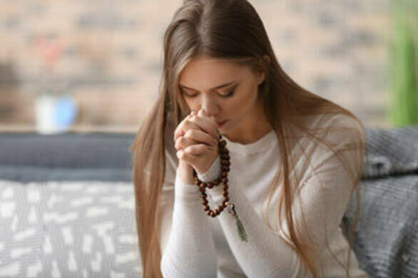 Woman praying rosary